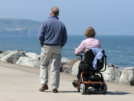 wheelchairs: Couple strolling on seaside promenade. Woman riding motorized wheelchair.