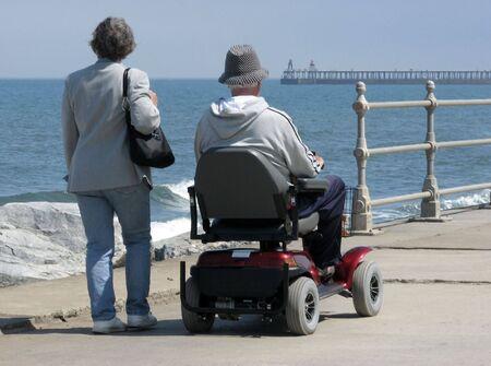 motorizado: Anciano montar silla de ruedas motorizada con la mujer en paseo marítimo.
