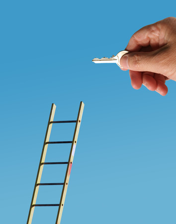 Male hand holding latchkey overlaid onto image of ladder. Stock Photo