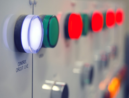 Close-up of electricity control panel with glowing lights. Shallow depth of field focussed on writing Stock Photo