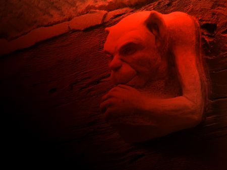 superstitions: Close up of gargoyle with red lighting effect Stock Photo