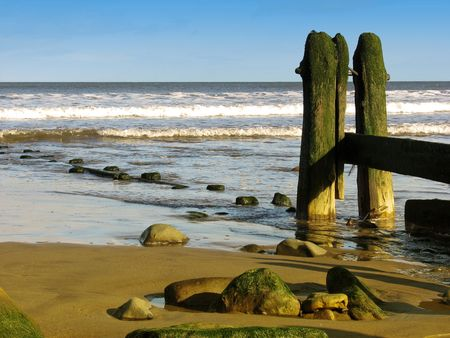 Landscape showing weathered sea defences on beach