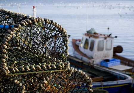 lobster boat: Stacked lobster baskets with out of focus fishing boats