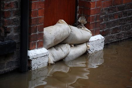 Sandbag barrier in doorway of flooded street in York. Stock Photo - 2482891