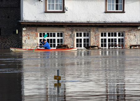 Canoeist paddles past flooded pub. River Ouse, York, North Yorkshire, UK.