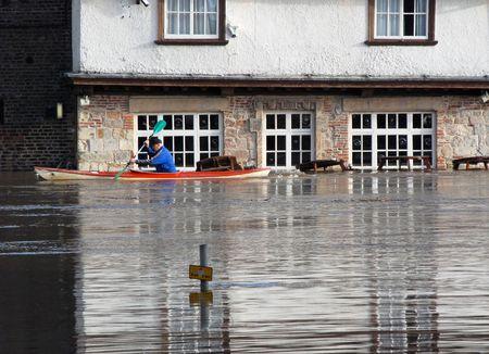 flood damage: Canoeist paddles past flooded pub. River Ouse, York, North Yorkshire, UK.