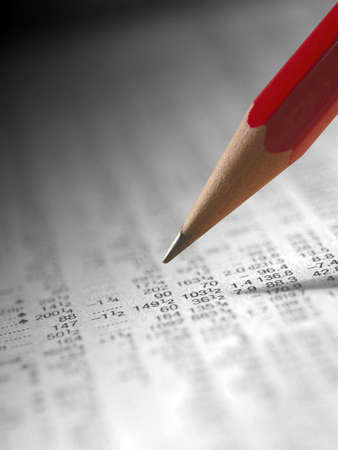 financial newspaper: Red pencil over monochrome financial newspaper Stock Photo