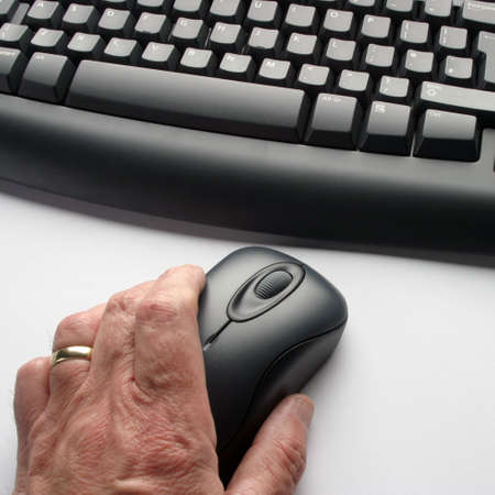 Elderly man using computer mouse photo