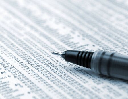 financial newspaper: Close up of pen resting on financial newspaper