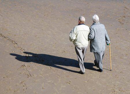 oap: Elderly couple walking on beach on sunny day Stock Photo