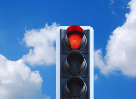obstruct: Red traffic light signal against cloudy blue sky