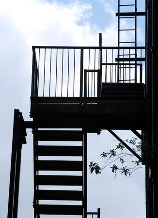 property ladder: Silhouette outline of fire escape steps against cloudy sky