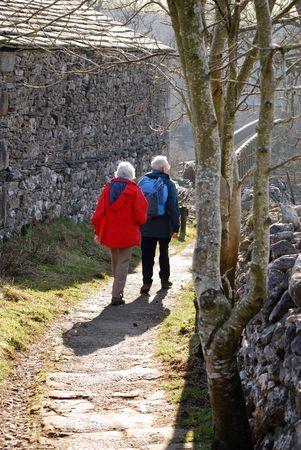 Elderly couple walking in country lane in Grassington, Yorkshire. Stock Photo - 3218490