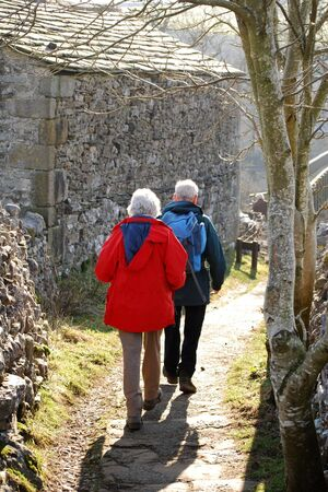 Elderly couple walk down country lan in Grassinton, Yorkshire, UK Stock Photo - 3243065