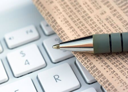 profiting: Financial newspaper rests on a computer laptop Stock Photo