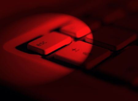 escape key: Red lighting effect applied to escape key on laptop keyboard Stock Photo