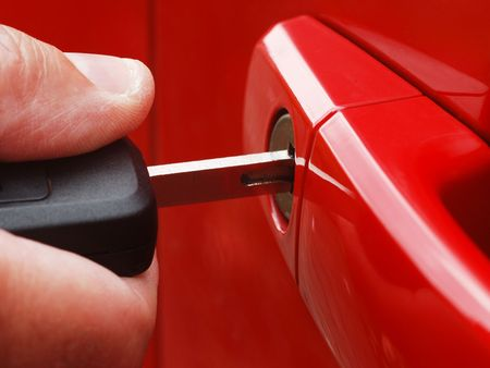 inserting: Extreme close-up of man inserting key into car lock