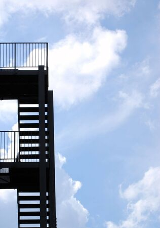 property ladder: Silhouette of steel fire escape with cloudy ble sky Stock Photo