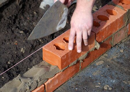 Close-up of builder laying bricks of new build photo