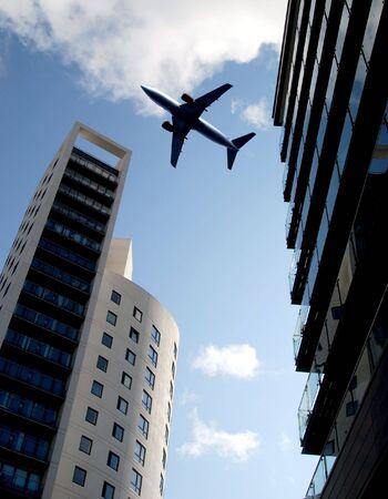 Jet passenger aircraft flies over tower blocks photo