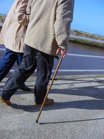 oap: Elderly couple take a stroll along Whitby pier Stock Photo
