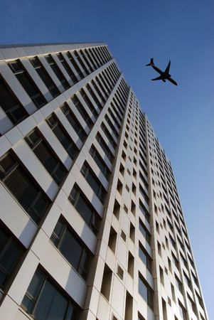 Airplane flies over tower block prior to landing photo