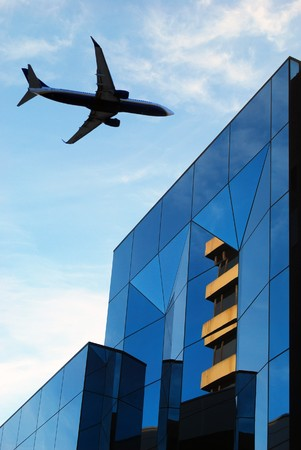 Airplane flie over building with glass reflections photo