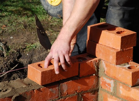 Construction worker laying bricks wall of building Stock Photo