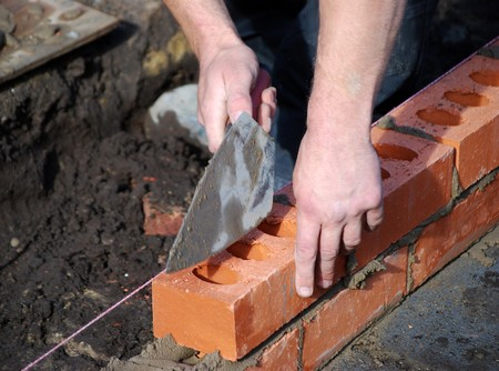 builders: Close-up of bricklayer building wall in new build Stock Photo