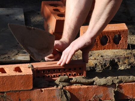 bricklayer: Close-up of bricklayer putting in air brick in wall