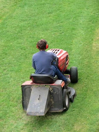 Male cutting grass while riding lawn mover photo