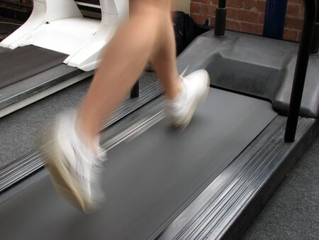 Man running on mechanical treadmill in gymnasium Stock Photo