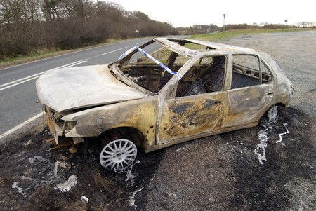 Burnt out abandoned car on side of road photo