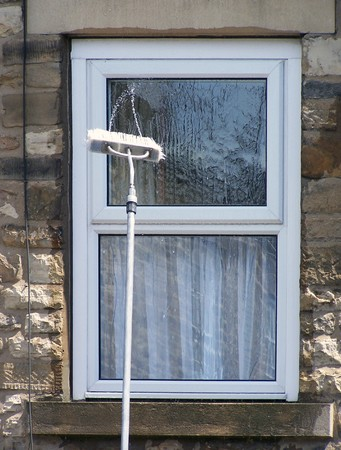 stone wash: Window cleaning brush on pole spays water onto glass Stock Photo