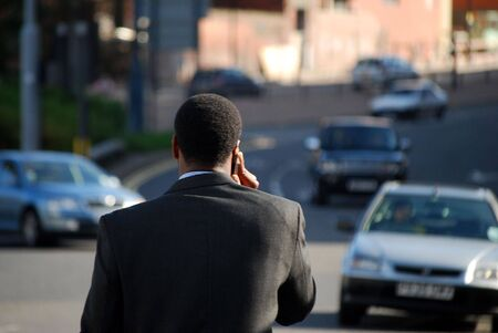 Telephoto view of man using telephone in busy street photo