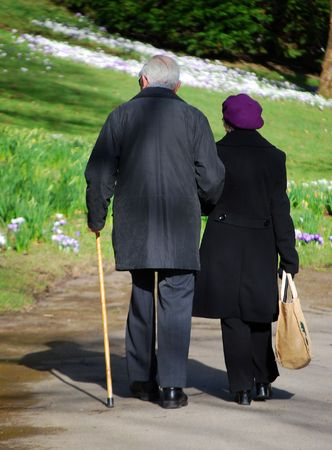 Silver haired couple enjoying walk in park