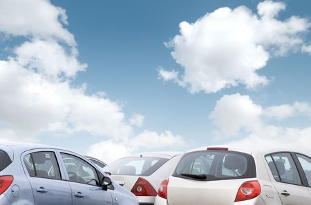 Close-up view of parked cars with coudy blue sky