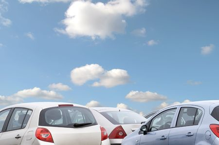 car parking: Telephoto view of parked cars with blue cloudy sky