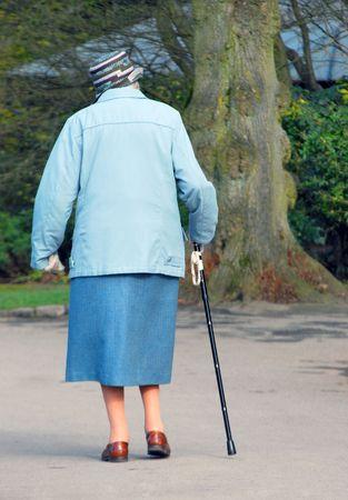 senioren wandelen: Bejaarde vrouw met stok wandelingen door park