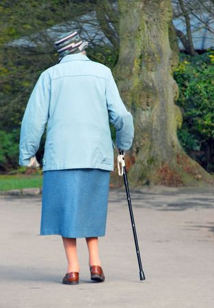 Elderly lady with stick walks through park