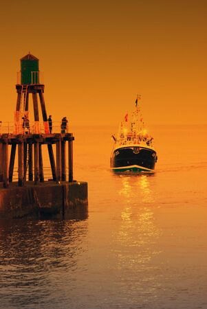 returning: Trawler fishing boat returning to Whitby harbor with  color overlay