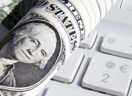 Close-up of US Dollar overlaid over laptop keys photo