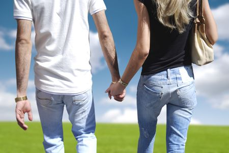 Young couple hold hands while walking through countryside photo