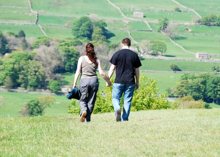 Young couple stroll through Yorkshire Dales countryside photo