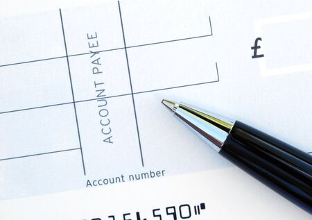 payee: Close-up of pen resting on blank cheque Stock Photo