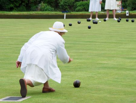 Telephoto view of middle age woman playing lawn bowls  Stock Photo