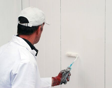 Male painter painting a white garage door