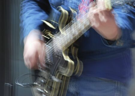 Close-up of male guitar player taken with slow shutter speed for effect Stock Photo