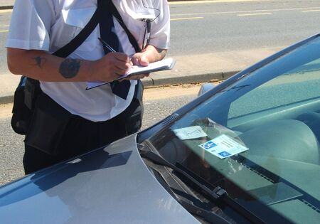 Traffic warden taking details from parked car showing disability permit Stock Photo