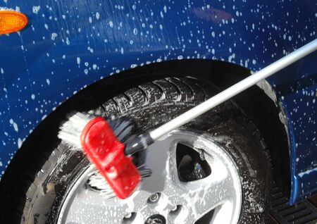 valeting: Close-up of brush cleaning wheel of car